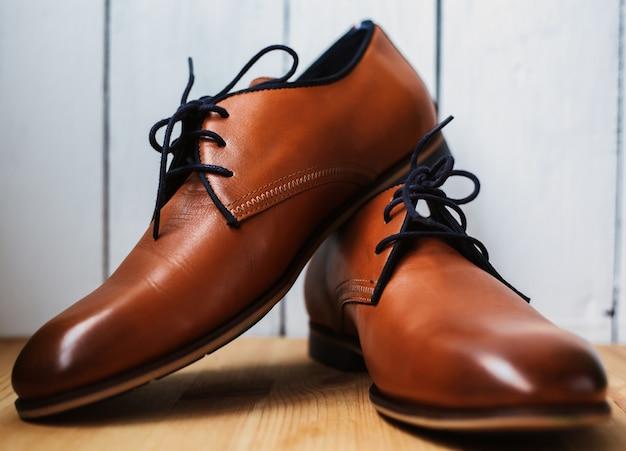 Модные кожаные мужские туфли на деревянный стол