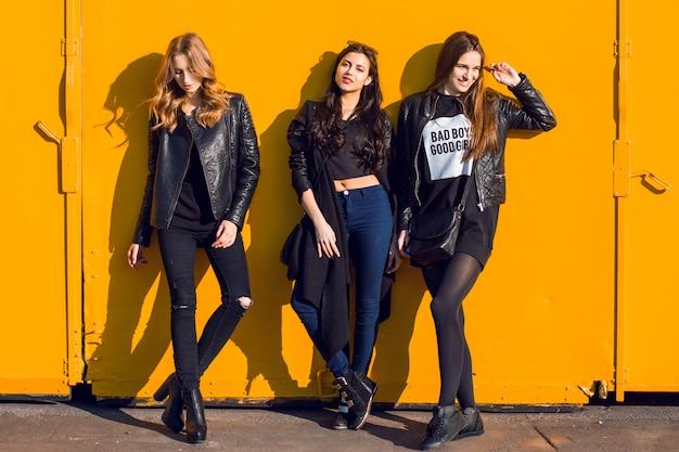 Фотография образа жизни моды трех стильных девушек в черном весеннем обмундировании представляя против розовой городской стены.