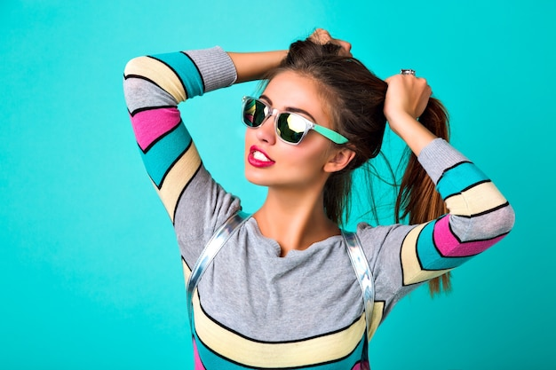 Fashion lifestyle portrait of joyful funny woman, sexy full lips, mirrored sunglasses, holding her hairs like two ponytails, spring colors, mint background. cute emotions, trendy woman.