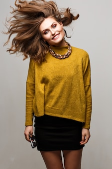 Fashion lifestyle portrait of young happy pretty woman laughing and having fun on the studio.