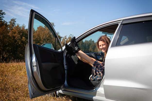 Fashion lifestyle portrait of young trendy woman dressed in pretty dress and boots posing, laughing and sitting in a car, enjoying an autumn day.