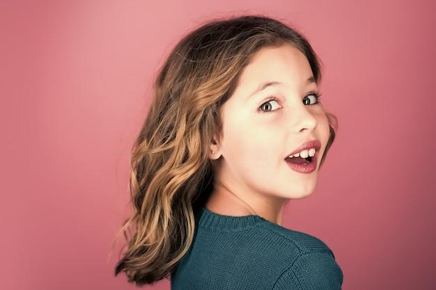 패션 작은 모델과 뷰티 룩. 회색 바탕에 예쁜 얼굴을 가진 세련 된 소녀입니다. 건강한 머리카락을 가진 아름다움과 아이 패션.
