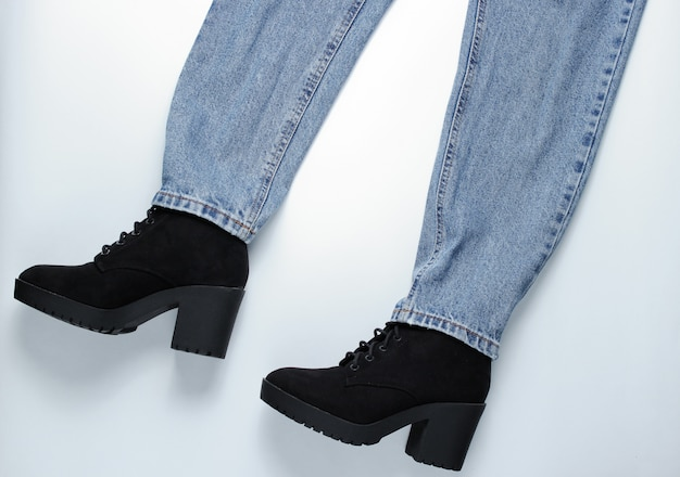 ファッションルック。灰色のテーブルにブーツとジーンズ。上面図