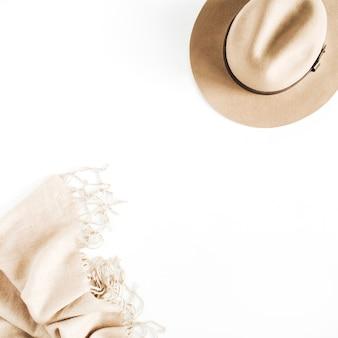 Модный образ с бледно-пастельно-бежевой шляпой и шарфом на белом фоне. плоская планировка, вид сверху
