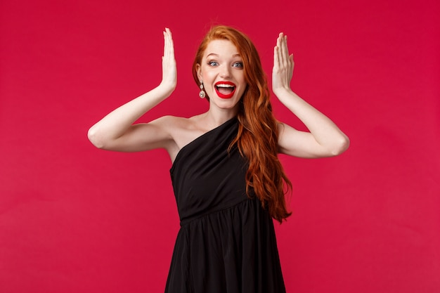 Fashion, luxury and beauty concept. portrait of surprised, happy and excited woman with ginger hair, evening black dress, looking amazed, open eyes and see awesome gift, smiling upbeat