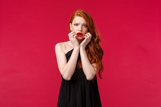 Fashion, luxury and beauty concept. portrait of timid and scared ginger girl in black dress feel unsafe or insecure, touch face frowning frightened, look concerned and worried , on a red wall