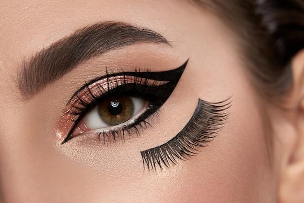 Модный макияж крупным планом с подводкой для глаз и накладными ресницами под