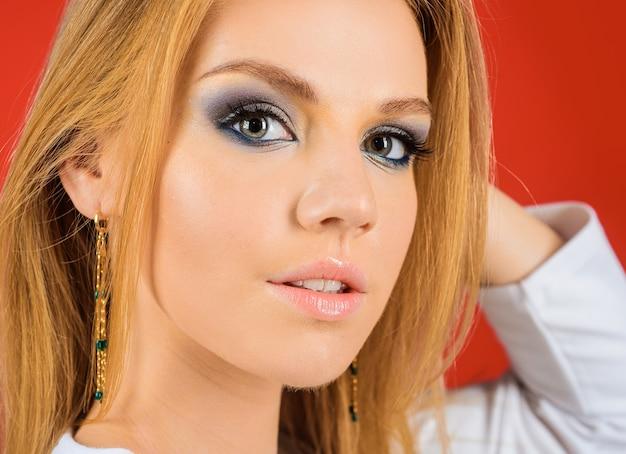 ファッションメイクや化粧品。明るい化粧の女の子。美容トレンド。ファッショナブルなジュエリー、イヤリング。