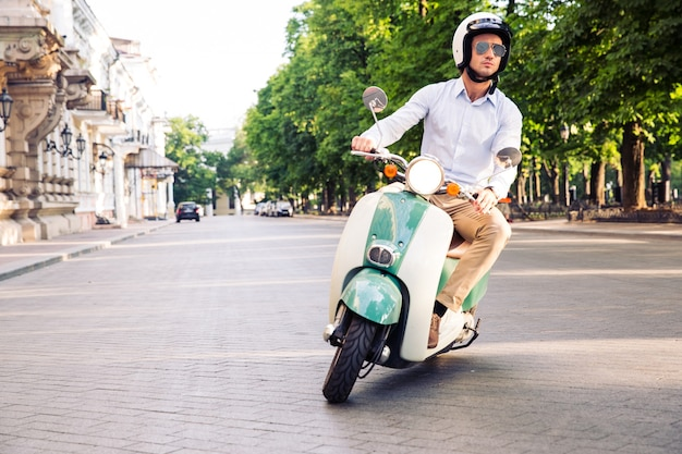 Fashion man driving a scooter