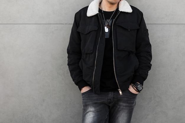 Модный мужчина в стильной одежде у серой стены