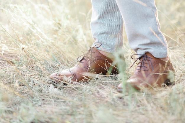 가 날에 잔디에 걷는 갈색 가죽 신발 패션 남자의 발.