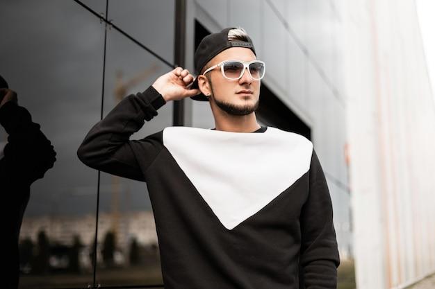 선글라스와 모자 패션 남자가 도시에서 산책