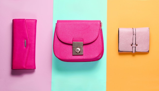 Fashion minimalism.  bags, leather wallets on a colored paper background. top view