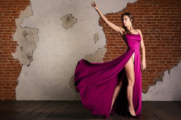 Модное платье искусства, элегантная женщина, стоящая в фиолетовом платье в стиле ретро