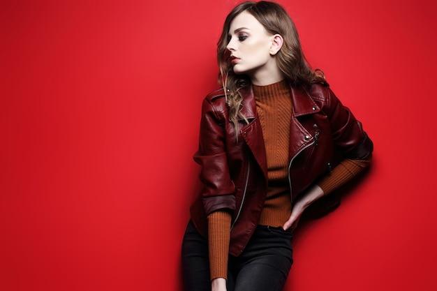 ファッションモデルの美しい若い女性。革のジャケット、スタジオショット、赤い背景