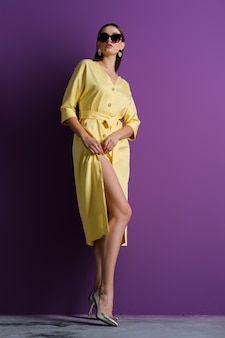 Fashion model in big sunglasses wearing yellow dress with unfastened buttons