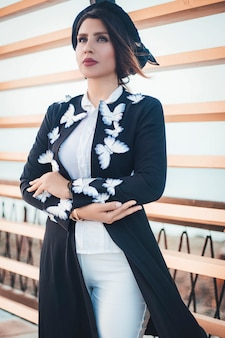 Fashion model in black knit jacket with butterflies and white jeans