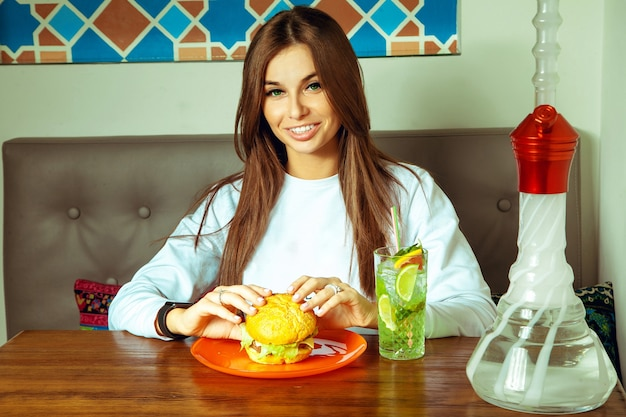 Fashion model at the cafe eating a hamburger and drinking cocktail