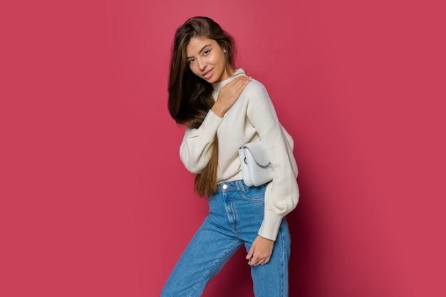 Modello di moda in pullover bianco accogliente e jeans casual in posa su sfondo rosa isolare. holding borsa a mano in ecopelle.