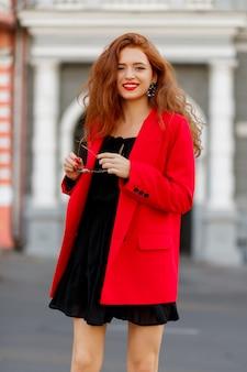 패션 모델은 최신 유행의 마모 및 액세서리를 보여줍니다. 캐주얼 레드 재킷, 블랙 쇼트 드레스.