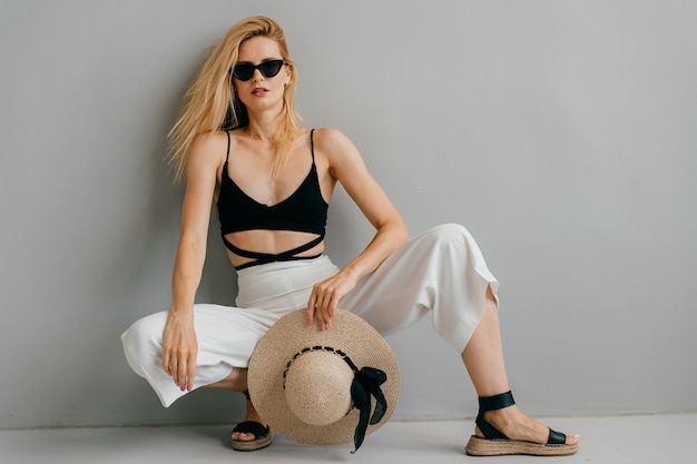 Fashion model in design black and white clothes with dark glasses and straw hat posed on grey color background