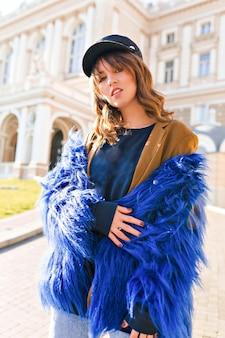 패션 모델은 건물이있는 거리에서 파란색 모피와 검은 모자 포즈를 입고 있습니다.