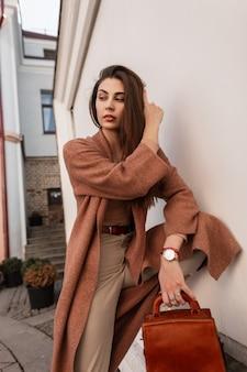 화이트 빈티지 야외 건물 근처 가죽 갈색 유행 핸드백과 베이지 색 유행 바지에 긴 세련 된 코트에서 패션 모델 우아한 젊은 여자. 도시에서 야외에서 포즈를 취하는 귀여운 도시 소녀