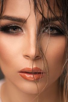 Fashion model in evening makeup with smokey eyes and suntanned tones