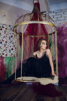 Fashion model in fantasy dress posing steel cage