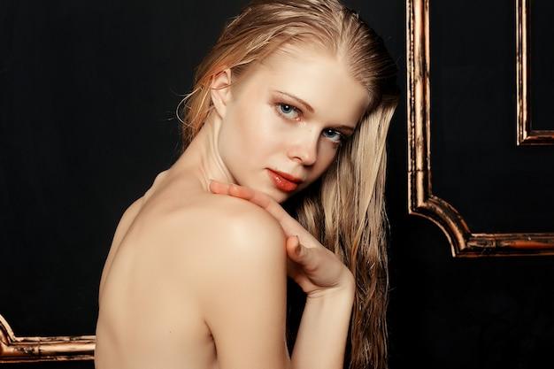 ナチュラル メイクと黒の背景に濡れた髪のファッション モデルの女の子