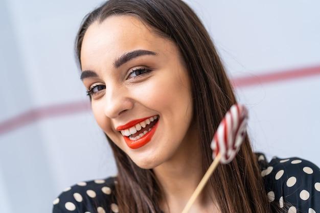 Девушка фотомодели с круглой конфетой в руках. красивая улыбающаяся молодая женщина. обрезанное фото.