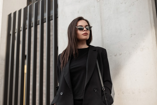 Fashion model gorgeous young woman in cool mirror sunglasses in fashionable black casual jacket in stylish t-shirt near modern building in city. american sexy girl in trendy youth outfit in street.