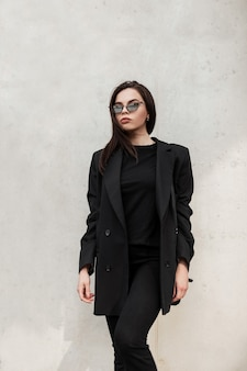 Fashion model gorgeous young woman in cool mirror sunglasses in fashionable black casual jacket in stylish t-shirt near modern white wall in city. american sexy girl in trendy youth outfit in street.