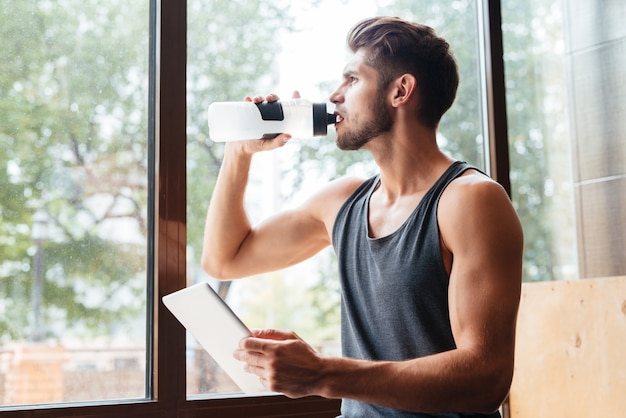 Fashion model in gym with bottle and tablet