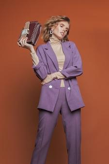 彼女の手でバッグを保持し、紫色の服でオレンジ色の背景にポーズをとってファッションモデル。