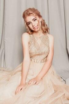 Фотомодель в красивом роскошном бежевом струящемся шифоновом платье, женщина в длинном летящем вечернем платье с платьем, потрясающая фэнтезийная модель. шелковая ткань развевается на ветру. атласная ткань струящаяся, волны платья