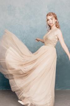 Фотомодель в красивом роскошном бежевом струящемся шифоновом платье, женщина в длинном летящем вечернем платье с платьем, потрясающая фэнтезийная модель. шелковая ткань развевалась на ветру. атласная ткань струящаяся, волны платья