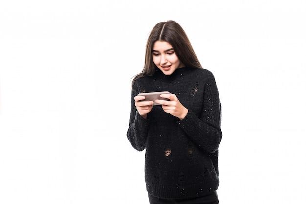 Фотомодель в темном свитере с телефоном на белом в студии