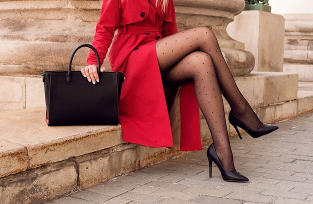 Фотомодель в красном пальто с большой черной сумкой в туфлях на высоком каблуке сидит на открытой лестнице. ноги крупным планом