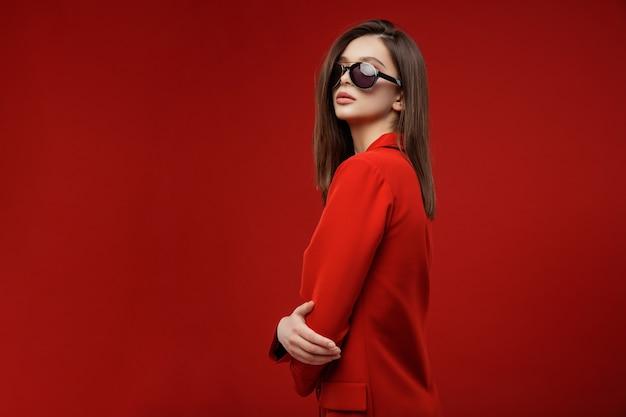 Фотомодель в красном костюме пиджак юбка солнцезащитные очки красивая молодая женщина красный фон