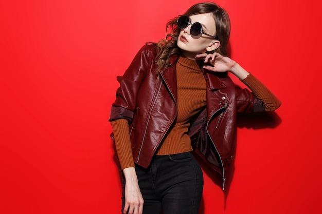 サングラスのファッションモデル、美しい若い女性。革のジャケット、スタジオショット、赤い背景