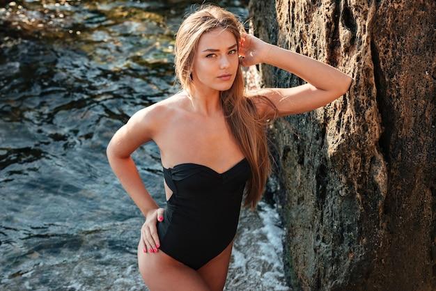 Фотомодель в купальнике. такая сексуальная девушка. на пляже. возле воды