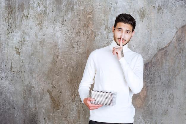 Фотомодель в белом свитере держит серебряную подарочную коробку и просит тишины.
