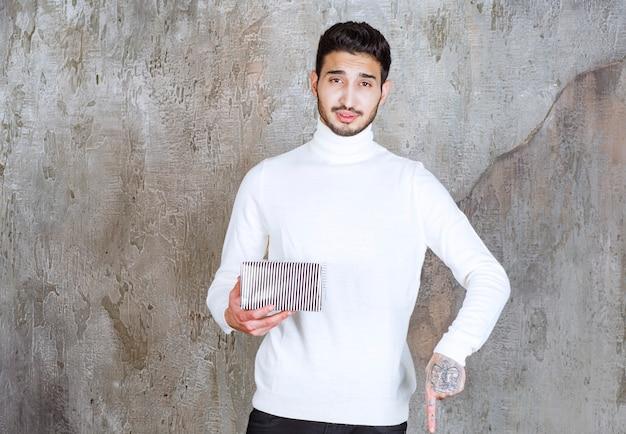 銀のギフトボックスを保持し、彼の隣の誰かに電話または招待する白いセーターのファッションモデル。