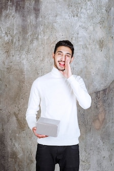 銀のギフトボックスを保持し、彼の隣の誰かを呼び出すか、招待する白いセーターのファッションモデル。