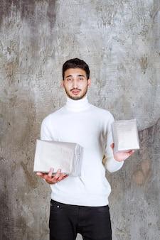 Фотомодель в белом свитере держит две серебряные подарочные коробки и выглядит задумчивой и смущенной.