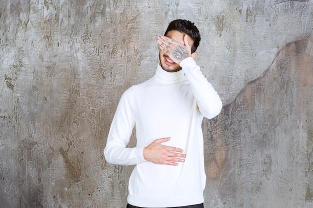 콘크리트 벽에 서있는 흰색 스웨터의 패션 모델은 졸리거나 피곤해 보입니다.