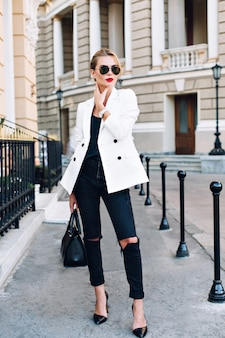 Fashion model is walking on street on heels. she wears sunglasses, ripped black jeans.