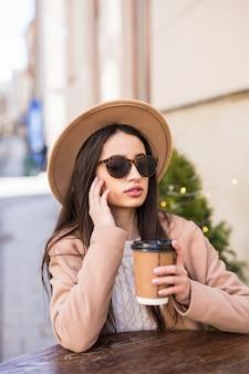 패션 모델 여자는 커피 컵 캐주얼 옷 어두운 선글라스 카페 드레스 테이블에 앉아있다