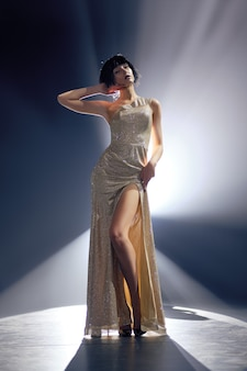 Fashion model in long dress with deep cut on the stage under key light
